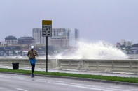 A jogger makes his way along Bayshore Blvd., in Tampa, Fla. as a wave breaks over a seawall, during the aftermath of Tropical Storm Elsa Wednesday, July 7, 2021. The Tampa Bay area was spared major damage as Elsa stayed off shore as it passed by. (AP Photo/John Raoux)