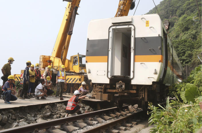 Workers try to remove a part of the derailed train near Taroko Gorge in Hualien, Taiwan on Saturday, April 3, 2021. The train partially derailed in eastern Taiwan on Friday after colliding with an unmanned vehicle that had rolled down a hill, killing and injuring dozens. Workers began removing some of the train cars and repair work also has begun on the tracks including the tunnel where part of the eight-car train crashed. (AP Photo/Chiang Ying-ying)