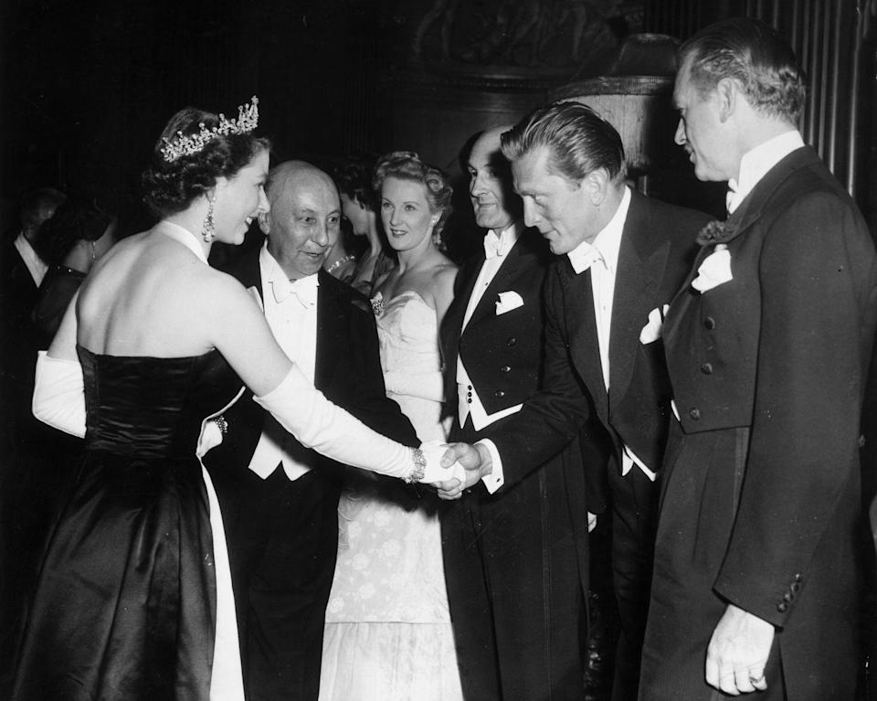 <p>While meeting Queen Elizabeth at the Royal Command premiere of <em>Because You're Mine</em> in London, Douglas bows and shakes her hand. </p>