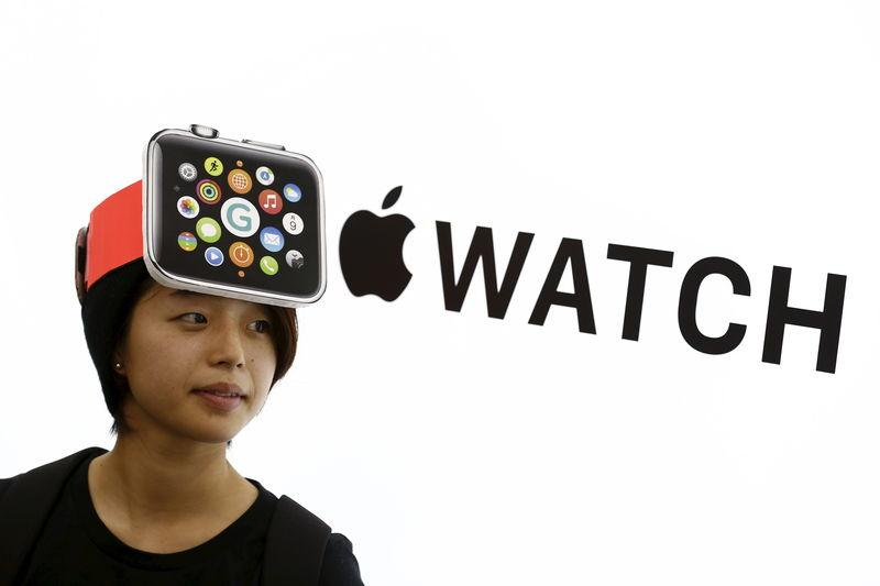 Woman wearing a mock-up Apple Watch stands in front of Apple sign at electronics store in Tokyo
