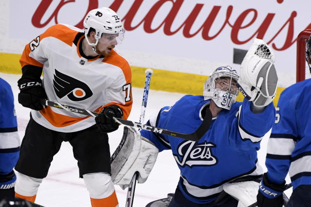 Winnipeg Jets goaltender Connor Hellebuyck (37) makes a glove-save on a shot as Philadelphia Flyers' David Kase (72) looks for the rebound during first-period NHL hockey game action in Winnipeg, Manitoba, Sunday, Dec. 15, 2019. (Fred Greenslade/The Canadian Press via AP)
