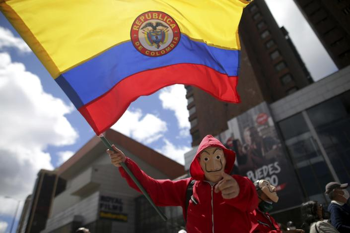 A masked man waves a Colombian flag during an anti-government march in Bogota, Colombia, Wednesday, May 19, 2021. Colombians have taken to the streets for weeks across the country after the government proposed tax increases on public services, fuel, wages and pensions. (AP Photo/Ivan Valencia)