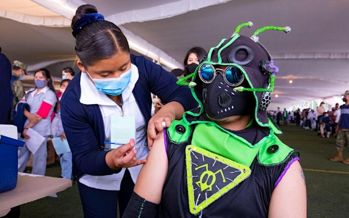 Young people - some dressed like monsters, Pikachu, Winnie the Pooh and Batman - receive their Covid-19 vaccines at the Xochimilco mayor's office in Mexico City, Mexico on 19 August 2021 - Carlos Ramirez/Shutterstock