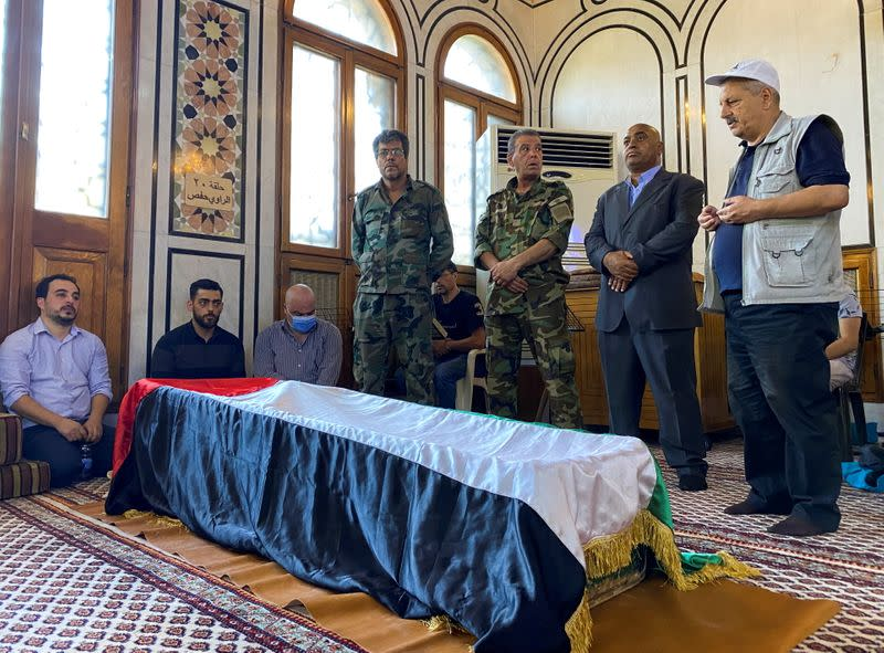 Mourners stand near the coffin of Ahmed Jibril, founder of pro-Syrian Palestinian guerrilla faction, during his funeral at a mosque in Damascus