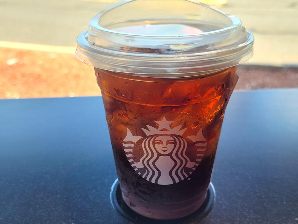 A cup of starbucks' cold brew on a black table outside