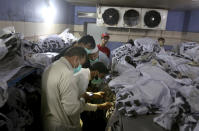 People identify body of their relative, who was killed in the Friday's plane crash, at a morgue in Karachi, Pakistan, Saturday, May 23, 2020. An aviation official says a passenger plane belonging to state-run Pakistan International Airlines carrying passengers and crew has crashed near the southern port city of Karachi. (AP Photo/Fareed Khan)