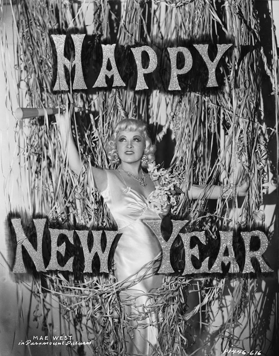 """<p>Vaudevillian sex symbol Mae West poses with a festive New Year's Eve setup in December 1936. Earlier that year, West starred in two films, <em>Klondike Annie</em> and <em>Go West, Young Man</em>. </p><p>Related: <a href=""""https://www.redbookmag.com/life/g30158490/new-years-eve-the-year-you-were-born/"""" rel=""""nofollow noopener"""" target=""""_blank"""" data-ylk=""""slk:What New Year's Eve Looked Like The Year You Were Born"""" class=""""link rapid-noclick-resp"""">What New Year's Eve Looked Like The Year You Were Born</a></p>"""