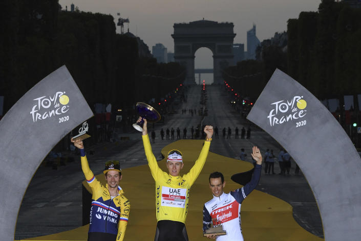 FILE - In this Sept.20, 2020 file photo, Tour de France winner Tadej Pogacar, wearing the overall leader's yellow jersey, second placed Primoz Roglic of Slovenia, left, and third placed Richie Porte of Australia, celebrate on the podium after the twenty-first and last stage of the Tour de France cycling race over 122 kilometers (75.8 miles), from Mantes-la-Jolie to Paris, France. (Stephane Mantey, Pool via AP, File)