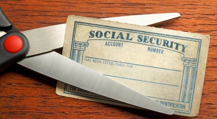 Scissors about to cut a Social Security card
