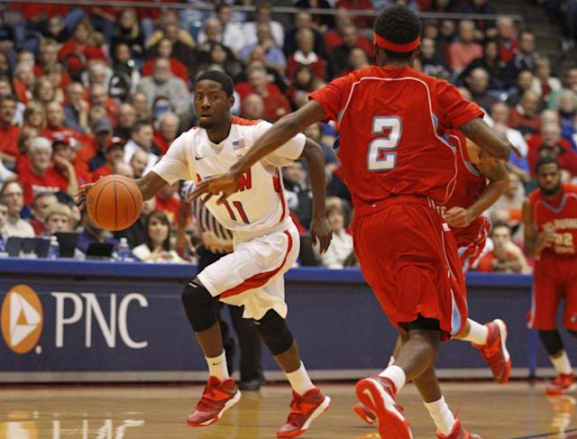 Dayton's Scoochie Smith (11) brings the ball upcourt in the first half of an NCAA college basketball game against Delaware State, Wednesday, Dec. 4, 2013, in Dayton, Ohio. Delaware State's Kendal Williams approaches Smith. (AP Photo/Skip Peterson)