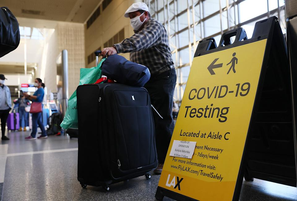 <p>People wait in line to check in near a sign pointing to a Covid-19 testing area in the Tom Bradley International Terminal at Los Angeles International Airport (LAX)</p> ((Getty Images))