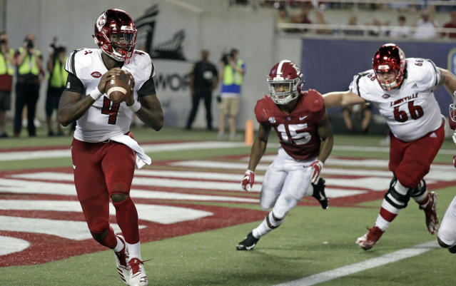 Louisville quarterback Jawon Pass (4) looks for a receiver as Alabama defensive back Xavier McKinney (15) gives chase during the first half of an NCAA college football game, Saturday, Sept. 1, 2018, in Orlando, Fla. (AP Photo/John Raoux)