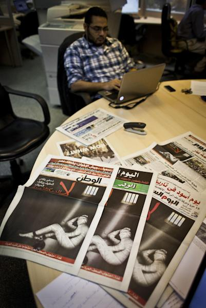 "An Egyptian journalist works at the editorial room of Al-Masry Al-Youm daily newspaper next to copies of Egypt's most prominent newspapers running black background front pages with Arabic that reads, ""no to dictatorship, tomorrow free newspapers will obscure to protest the freedom's restrictions,"" and a picture of a man wrapped in newspapers with his feet cuffed, in Cairo, Egypt, Monday, Dec. 3, 2012. Eleven Egyptian newspapers are planning to suspend publication on Tuesday to protest against President Mohammed Morsi's decision to call a constitution referendum on 15 December. (AP Photo/Nasser Nasser)"