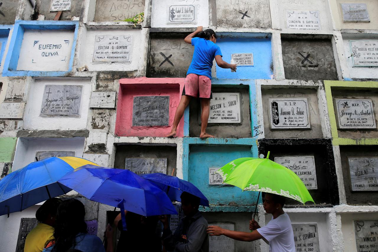 <p>People visit apartment-style tombs of their loved ones during the observance of All Saints' Day at Navotas Public cemetery in Metro Manila, Philippines, Nov. 1, 2017. (Photo: Romeo Ranoco/Reuters) </p>