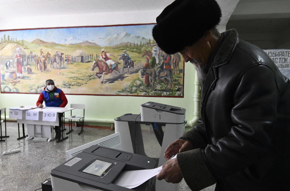 A man casts his ballot during the presidential elections in Gornaya Maevka village, about 25 kilometers (16 miles) south-west of Bishkek, Kyrgyzstan, Sunday, Jan. 10, 2021. Voters in Kyrgyzstan cast ballots in an election that will also determine how much power the next president has. The Sunday vote follows the ouster of the nation's previous president in October. President Sooronbai Jeenbekov was forced to step down on Oct. 15 under pressure from demonstrators who challenged the results of a parliamentary vote earlier that month. (AP Photo/Vladimir Voronin)