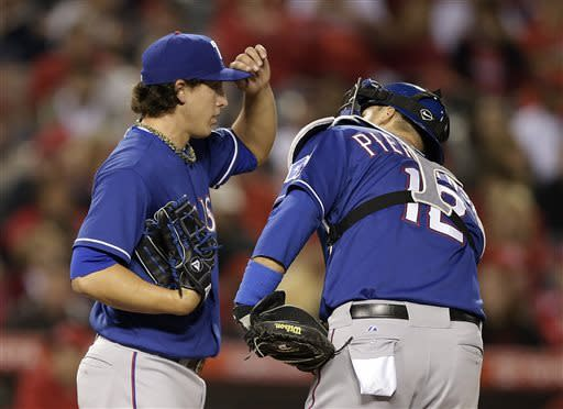 Texas Rangers starting pitcher Derek Holland, left, chats with catcher A.J. Pierzynski during the fourth inning of a baseball game against the Los Angeles Angels in Anaheim, Calif., Monday, April 22, 2013. (AP Photo/Jae C. Hong)