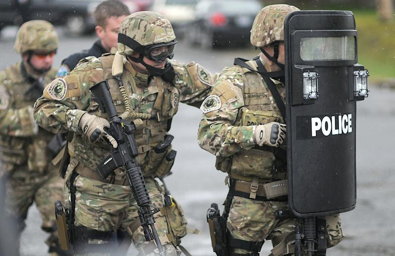 Aberdeen SWAT team officers carefully approach a home in Montesano where they believed a suspect in the shooting at the Grays Harbor County Courthouse may be hiding in Montesano, Wash. Friday March 9, 2012. Authorities spent two hours containing the home, which was later found to be empty (AP Photo/The Daily World, Jacob Jones).