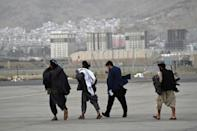 Taliban fighters walk on the tarmac after a Qatar Airways aircraft took off from the airport in Kabul on September 9, 2021 (AFP/WAKIL KOHSAR)