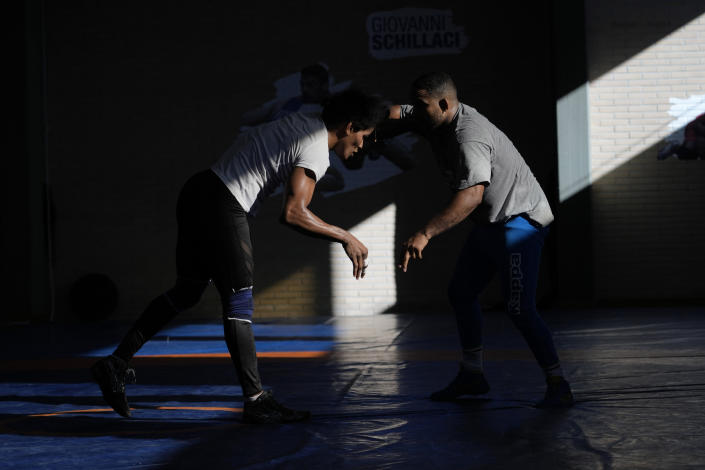 Guinean wrestler Fatoumata Yarie Camara, left, compete with Wilfredo Garcia, trainer of the Italian female wrestling team during an afternoon training session in Ostia, near Rome, Monday, July 5, 2021. A West African wrestler's dream of competing in the Olympics has come down to a plane ticket. Fatoumata Yarie Camara is the only Guinean athlete to qualify for these Games. She was ready for Tokyo, but confusion over travel reigned for weeks. The 25-year-old and her family can't afford it. Guinean officials promised a ticket, but at the last minute announced a withdrawal from the Olympics over COVID-19 concerns. Under international pressure, Guinea reversed its decision. (AP Photo/Alessandra Tarantino)