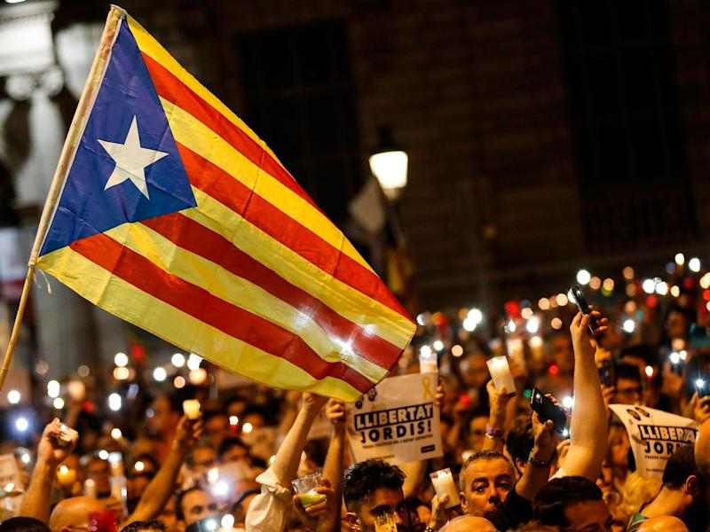 People hold candles and a Catalan pro-independence 'Estelada' flag during a demonstration in Barcelona against the arrest of two Catalan separatist leaders: PAU BARRENA/AFP/Getty Images