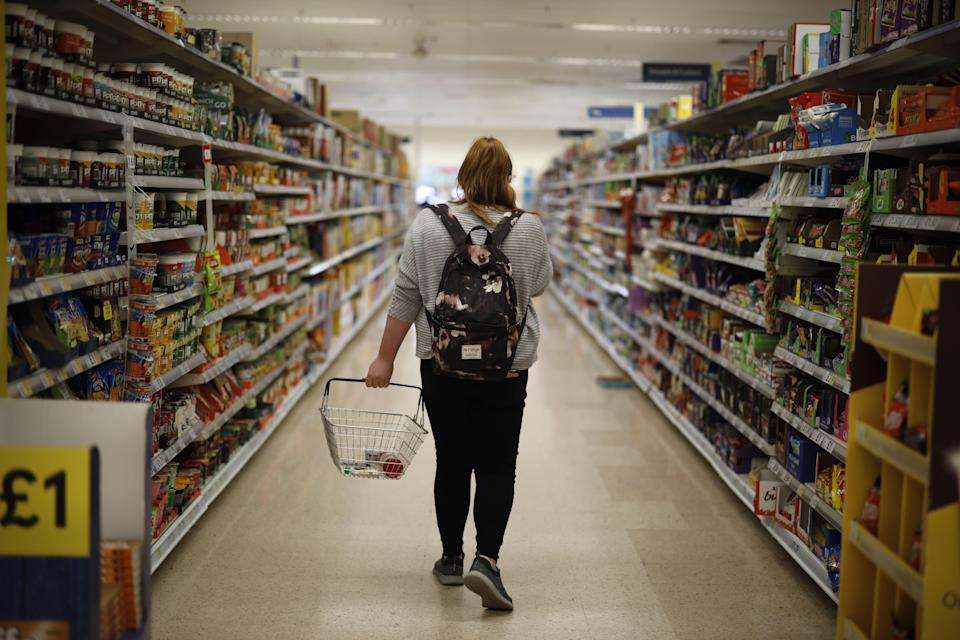 <p>A shopper browses an aisle for groceries at a Tesco Superstore in south London</p> (AFP via Getty Images)