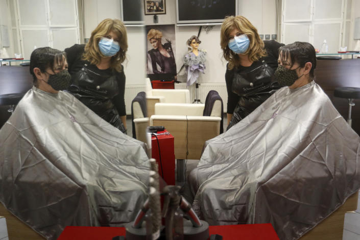 Hairdresser Andrea Roder is reflected in a mirror while posing with a customer in Budapest, Hungary, Wednesday April 7, 2021. Hungary's government lifted several lockdown restrictions on Wednesday, even as some doctors and medical experts urged caution after a record-breaking day of COVID-19 deaths, a move that came as Hungary reached 2.5 million first-dose vaccinations, a benchmark the government set for when a gradual reopening could move forward. (AP Photo/Laszlo Balogh)
