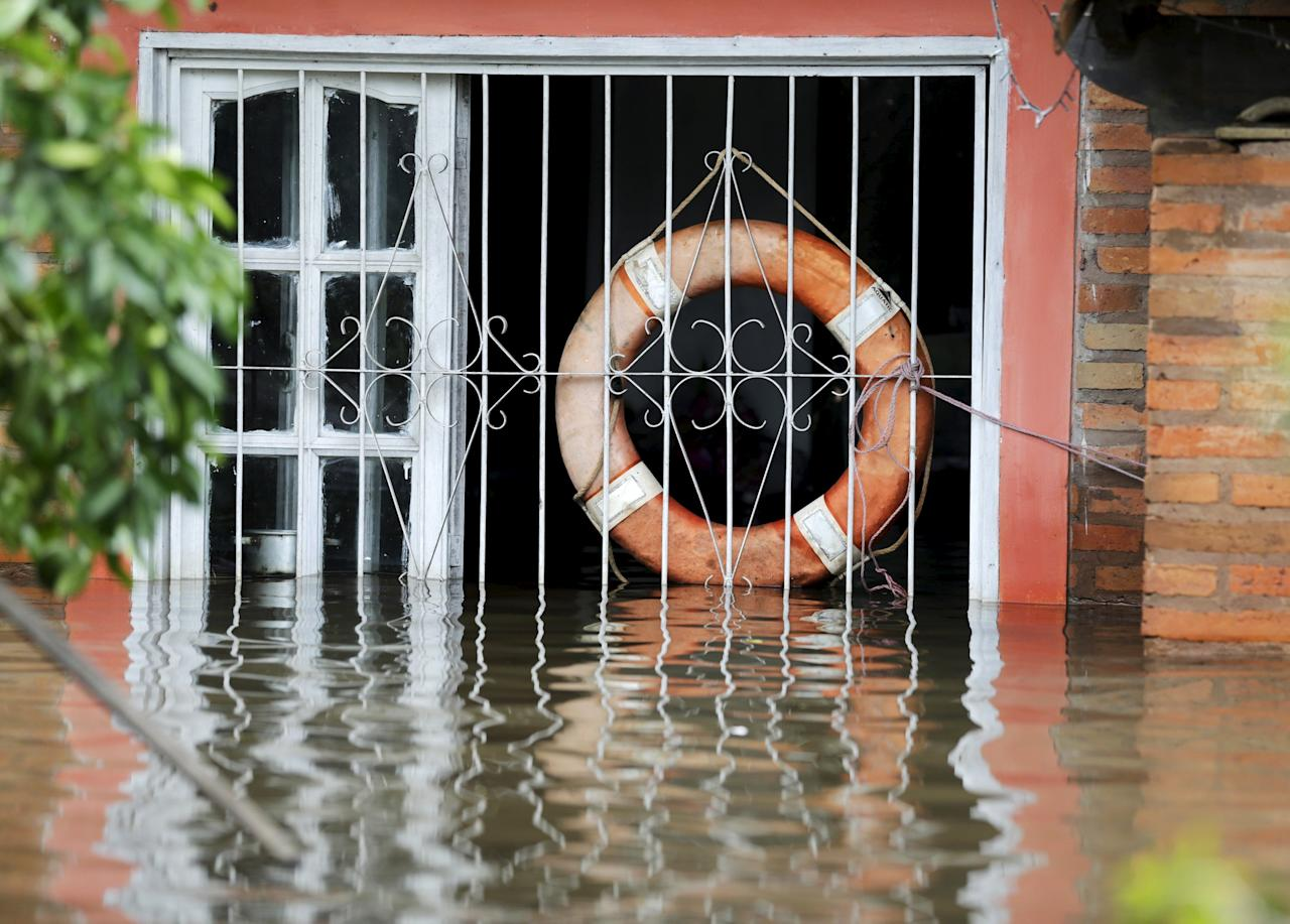 A lifebouy hangs from a window in a flooded house in Asuncion, December 27, 2015. More than 100,000 people have had to evacuate from their homes in the bordering areas of Paraguay, Uruguay, Brazil and Argentina due to severe flooding in the wake of heavy summer rains brought on by El Niño, authorities said on Saturday. REUTERS/Jorge Adorno