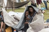 People gather after spending the night outside in the aftermath of the earthquake, facing the severe inclement weather of Tropical Storm Grace near Les Cayes, Haiti on August 17, 2021
