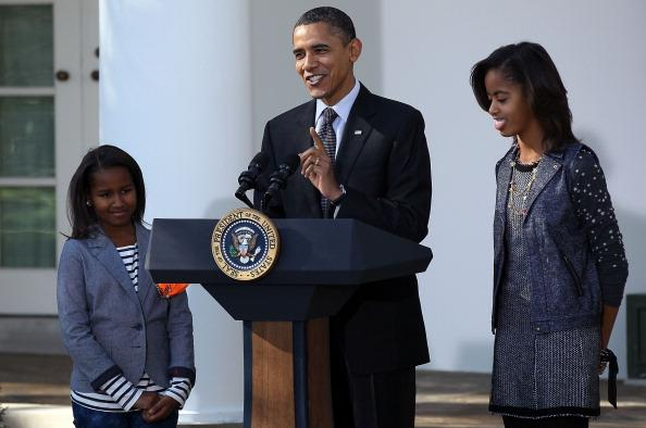 U.S. President Barack Obama speaks during a ceremony, where he pardoned the National Thanksgiving Turkey, named Apple, with daughters Sasha (L) and Malia (R) in the Rose Garden November 24, 2010 in Washington, DC. Obama also pardoned Cider, Apple's alternate. After the event, Apple and Cider will be taken to a new residence at George Washington's Mount Vernon Estate and Gardens. (Photo by Win McNamee/Getty Images)