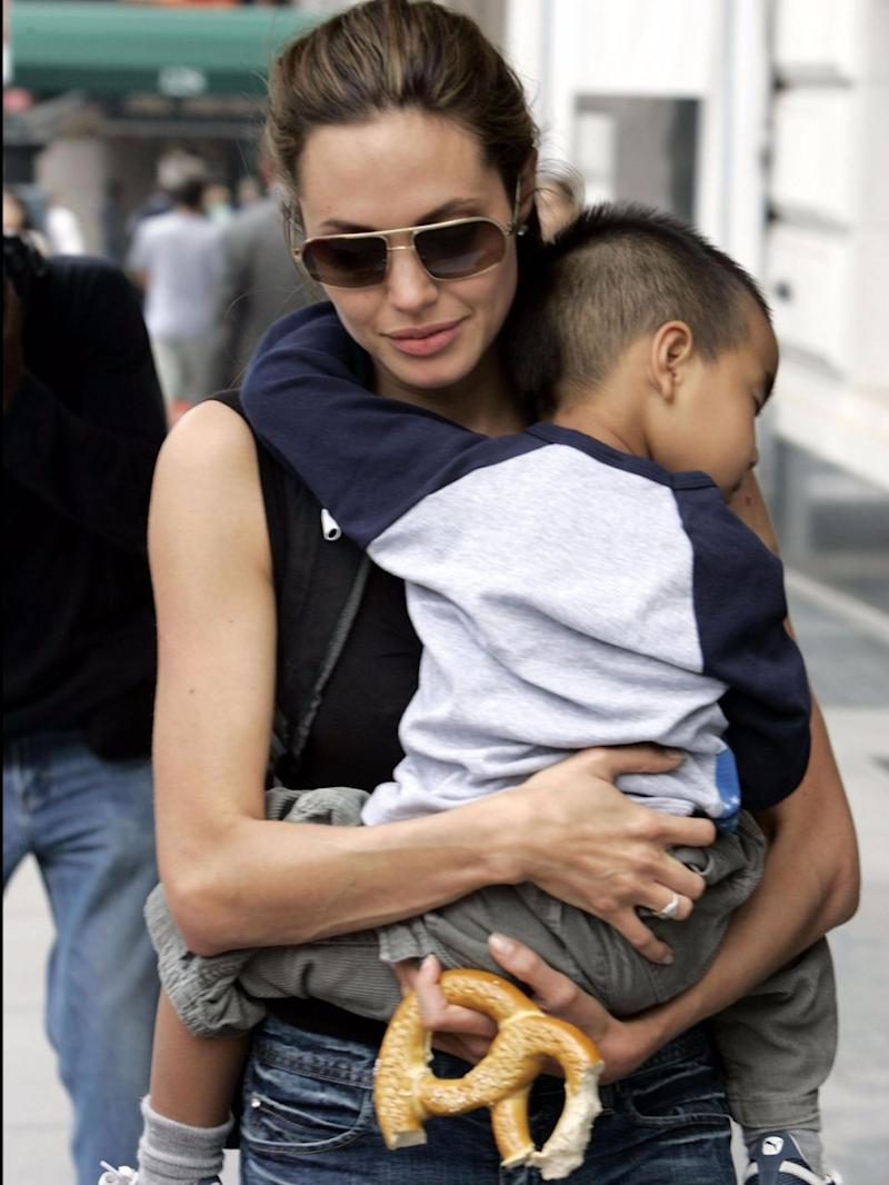 Angelina carrying a very tiny Maddox when he was younger. Source: Getty