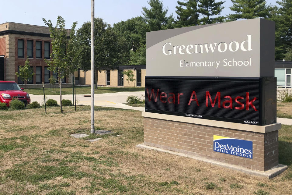 FILE - In this Sept. 17, 2020 file photo, a sign outside of Greenwood Elementary School promotes mask-wearing in Des Moines, Iowa. With COVID-19 cases soaring nationwide, school districts across the U.S. are yet again confronting the realities of a polarized country and the lingering pandemic as they navigate mask requirements, vaccine rules and social distancing requirements for the fast-approaching new school year. (AP Photo/Scott McFetridge, File)