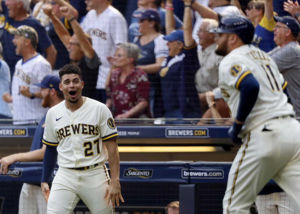 Milwaukee Brewers' Willy Adames(27) reacts to Rowdy Tellez' , right, three-RBI pinch hit home run against the Pittsburgh Pirates during the seventh inning of a baseball game Wednesday, Aug. 4, 2021, in Milwaukee. (AP Photo/Jeffrey Phelps)