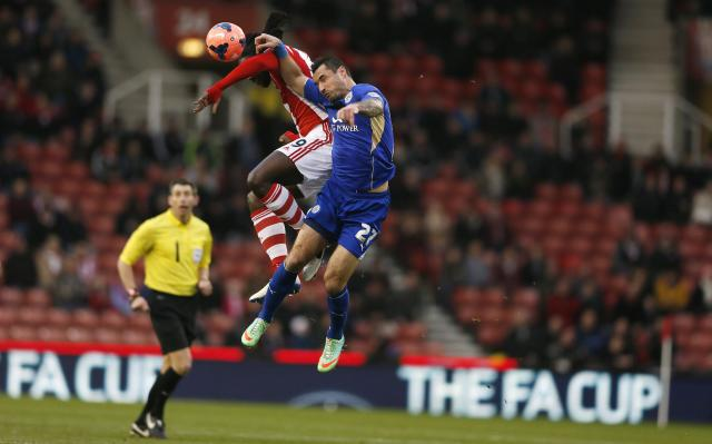 Leicester City's Marcin Wasilewski (R) challenges Stoke City's Kenwyne Jones during their English FA Cup third round soccer match at the Britannia stadium in Stoke-on-Trent, central England January 4, 2014. REUTERS/Stefan Wermuth (BRITAIN - Tags: SPORT SOCCER TPX IMAGES OF THE DAY)