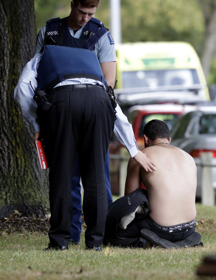 <p>Police console a man outside a mosque in central Christchurch, New Zealand. (AP Photo/Mark Baker) </p>
