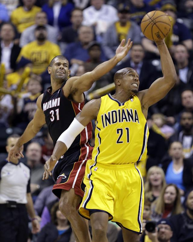 Indiana Pacers forward David West, right, grabs a long rebound in front of Miami Heat forward Shane Battier in the second half of an NBA basketball game in Indianapolis, Tuesday, Dec. 10, 2013. The Pacers won 90-84. (AP Photo/Michael Conroy)