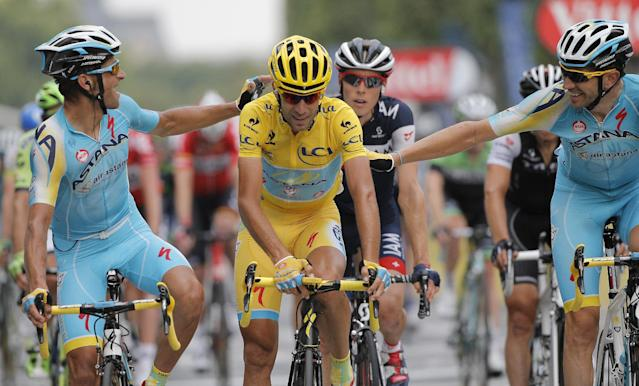 Italy's Vincenzo Nibali, centre, is congratulated by teammates as he crosses the finish line to win the 2014 Tour de France after the twenty-first and last stage of the Tour de France cycling race over 137.5 kilometers (85.4 miles) with start in Evry and finish in Paris, France, Sunday, July 27, 2014. (AP Photo/Christophe Ena)