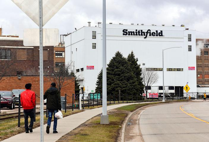 Employees walk into work March 24 at the Smithfield Foods plant in Sioux Falls, S.D.