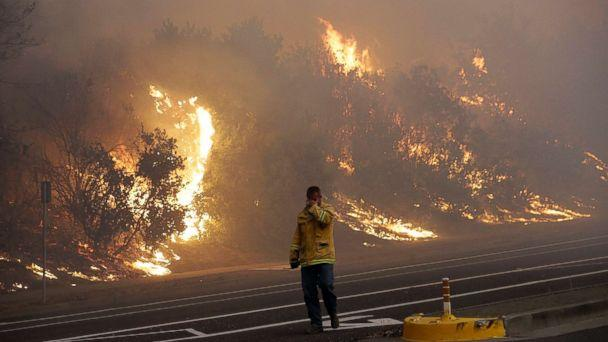 PHOTO: A firefighter covers his eyes as he walks past a burning hillside in Santa Rosa, Calif., Oct. 9, 2017. (Jeff Chiu/AP)
