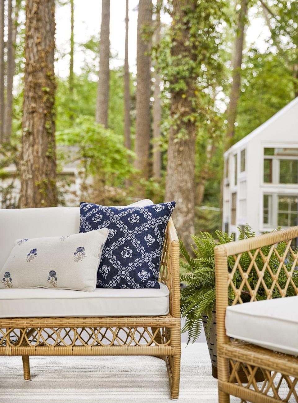"""<p>A mix of patterned pillows atop the rattan furniture's crisp white cushions—all made of outdoor-friendly, indoor-pretty <a href=""""https://www.sunbrella.com/outdoor-living"""" rel=""""nofollow noopener"""" target=""""_blank"""" data-ylk=""""slk:Sunbrella"""" class=""""link rapid-noclick-resp"""">Sunbrella</a> fabrics—brings practicality without sacrificing style.</p><p><strong>Get the Look: </strong><br><strong>Rug:</strong> <a href=""""https://www.colonialmills.com/collection-colors/1232"""" rel=""""nofollow noopener"""" target=""""_blank"""" data-ylk=""""slk:Sunbrella &quot;Southport Stripe&quot; in Ash by Colonial Mills"""" class=""""link rapid-noclick-resp"""">Sunbrella """"Southport Stripe"""" in Ash by Colonial Mills</a><strong><br>Sofa:</strong> <a href=""""https://go.redirectingat.com?id=74968X1596630&url=https%3A%2F%2Fwww.serenaandlily.com%2Fcapistrano-sofa---light-dune%2Fm13244.html%23q%3Dcapistrano%26start%3D6&sref=https%3A%2F%2Fwww.countryliving.com%2Fhome-design%2Fhouse-tours%2Fg36730466%2Fmakeover-takeover-backyard%2F"""" rel=""""nofollow noopener"""" target=""""_blank"""" data-ylk=""""slk:&quot;Capistrano&quot; (upholstered in Sunbrella's &quot;Canvas White&quot; fabric) by Serena & Lily"""" class=""""link rapid-noclick-resp"""">""""Capistrano"""" (upholstered in Sunbrella's """"Canvas White"""" fabric) by Serena & Lily</a><strong><br></strong><strong>White Patterned Pillows: </strong><a href=""""https://go.redirectingat.com?id=74968X1596630&url=https%3A%2F%2Fwww.ballarddesigns.com%2Foutdoor-fashion-throw-pillow---select-colors%2F597837&sref=https%3A%2F%2Fwww.countryliving.com%2Fhome-design%2Fhouse-tours%2Fg36730466%2Fmakeover-takeover-backyard%2F"""" rel=""""nofollow noopener"""" target=""""_blank"""" data-ylk=""""slk:Sunbrella &quot;Anais Indigo&quot; from Ballard Designs"""" class=""""link rapid-noclick-resp"""">Sunbrella """"Anais Indigo"""" from Ballard Designs</a><br><strong>Navy Patterned Pillows:</strong> <a href=""""https://go.redirectingat.com?id=74968X1596630&url=https%3A%2F%2Fwww.shopterrain.com%2Fproducts%2Ffloral-diamond-outdoor-pillow&sref=https%3A%2F%2Fwww.countryliving.com%2"""