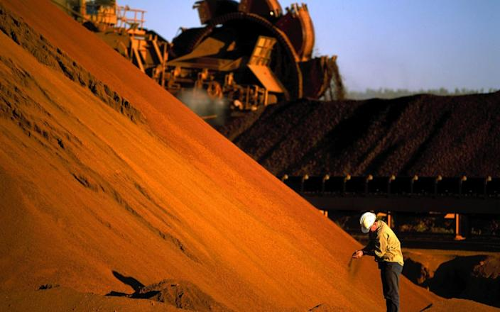 A worker inspects iron ore stockpiles at Rio Tinto's location of Marandoo in western Australia - Getty Images/Fairfax Media