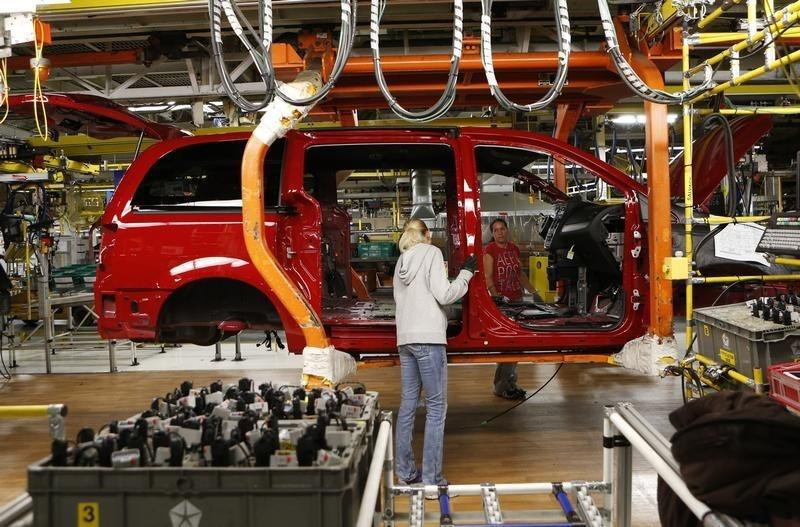 Fiat Chrysler assembly workers work on a partially assembled minivan at the Windsor Assembly Plant in Windsor, Ontario,
