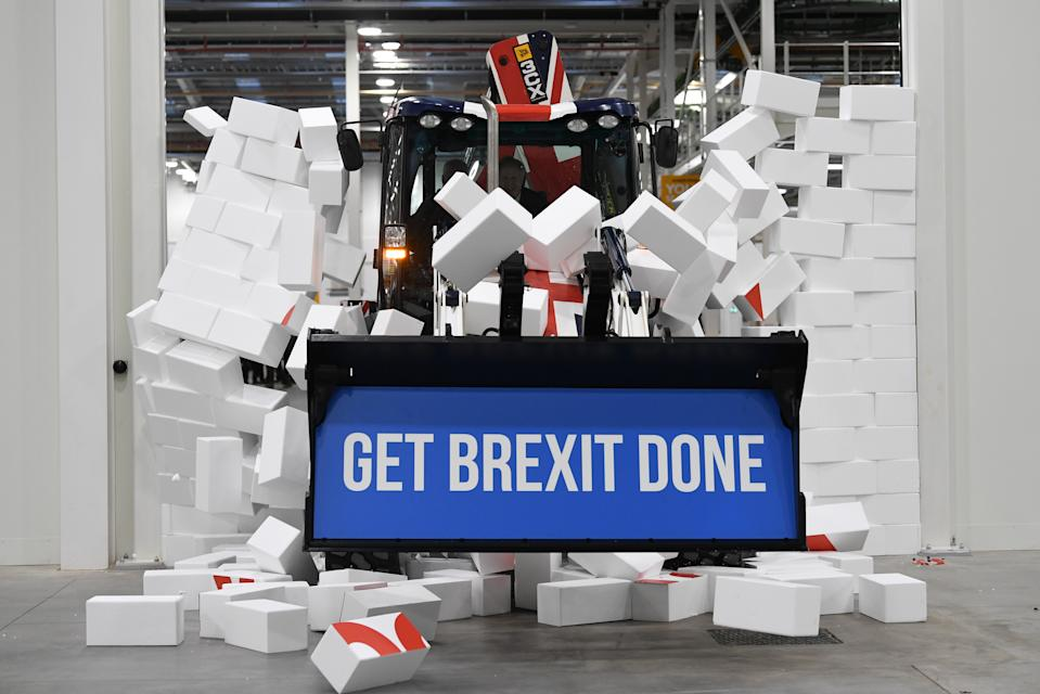 """Prime Minister Boris Johnson drives a Union flag-themed JCB, with the words """"Get Brexit Done"""" inside the digger bucket, through a fake wall emblazoned with the word """"Gridlock"""", during a visit to JCB cab manufacturing centre in Uttoxeter, while on the General Election campaign trail."""