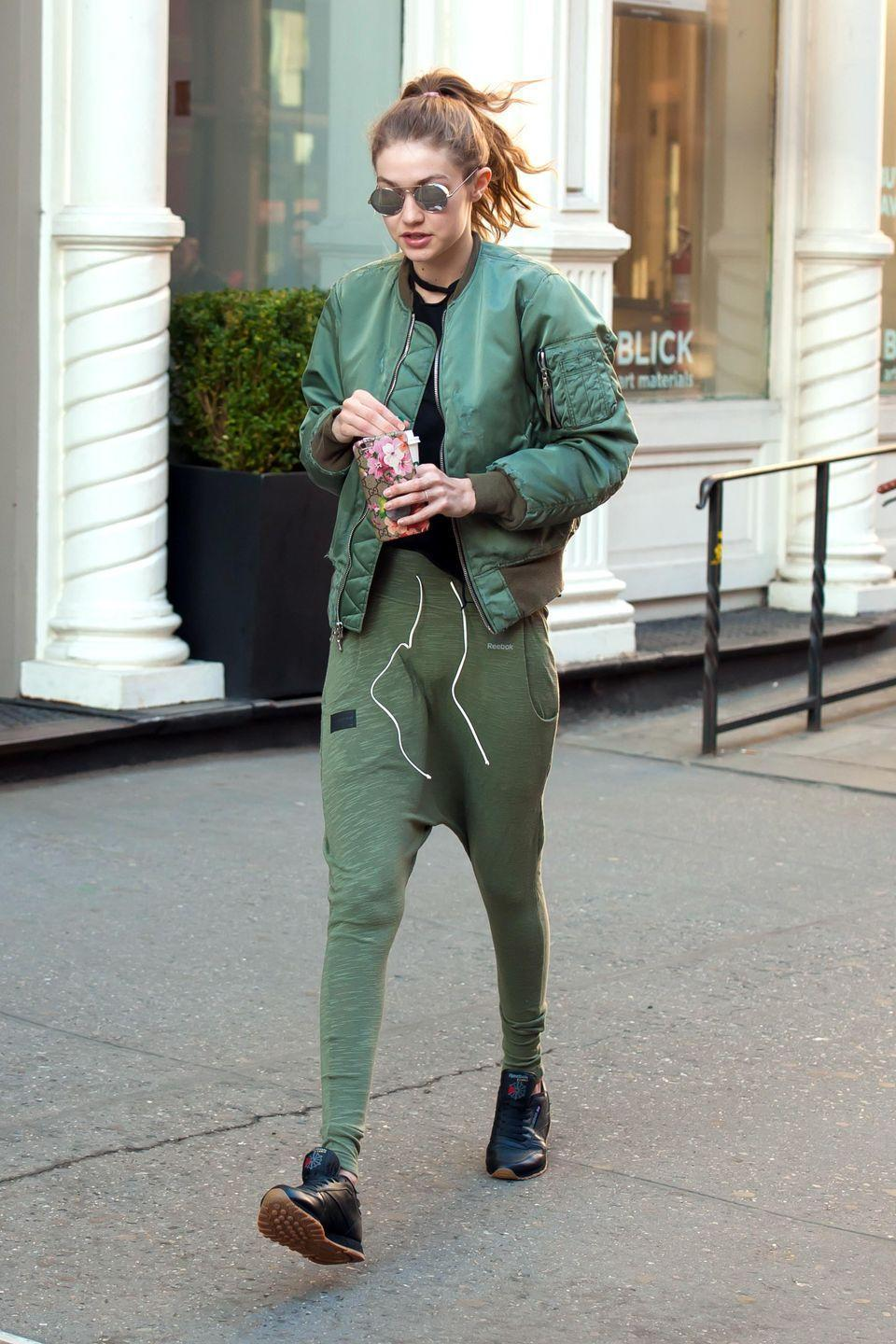 <p>In a green Unravel bomber with matching Reebok sweatpants and black Reebok sneakers with silver Linda Farrow sunglasses and a Gucci phone case while out in New York City. </p>