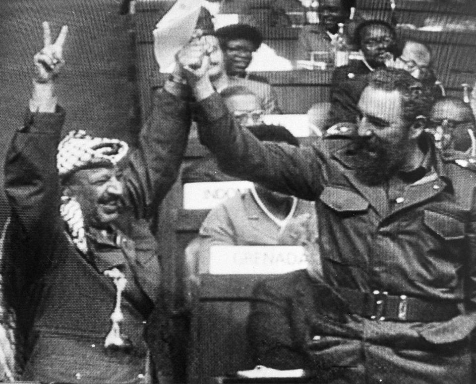 <p>Cuban Prime Minister Fidel Castro, right, and P.L.O leader Yasser Arafat join hands following the P.L.O. closing speech at the final session of the 7th Non-Aligned Summit conference, March 13, 1983 in New Delhi. (AP Photo/Indian TV) </p>