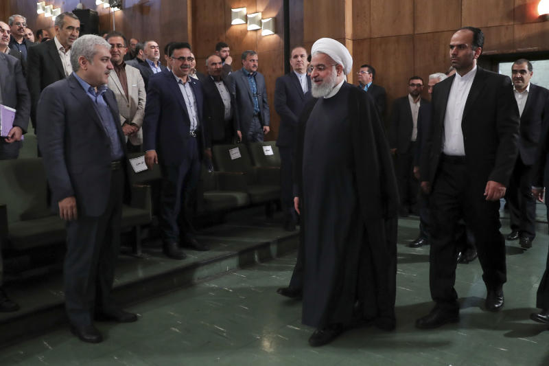 In this photo released by official website of the office of the Iranian Presidency, President Hassan Rouhani, center, arrives to attend a ceremony to mark the start of the Iranian academic year at Tehran University, Iran, Sunday, Oct. 14, 2018. Rouhani on Sunday tried to downplay U.S. sanctions targeting the country's vital oil and gas sector that are set to be restored next month. (Iranian Presidency Office via AP)