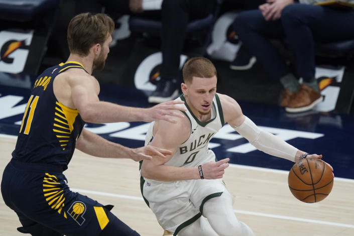 Milwaukee Bucks' Donte DiVincenzo (0) is defended by Indiana Pacers' Domantas Sabonis (11) during the second half of an NBA basketball game Thursday, May 13, 2021, in Indianapolis. (AP Photo/Darron Cummings)