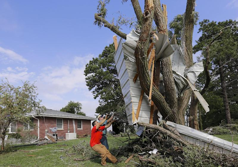Residents try to free a house panel from where it was lodged against a tree following a tornado in Bennet, Neb., Friday, Oct. 4, 2013. Powerful storms crawled into the Midwest on Friday, dumping heavy snow in South Dakota, spawning a tornado in Nebraska and threatening dangerous thunderstorms from Oklahoma to Wisconsin. (AP Photo/Nati Harnik)