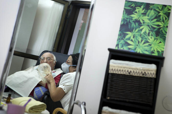 In this photograph made on Tuesday, Oct. 30, 2012, Rom Germad inhales medical cannabis at the old age nursery home in kibbutz Naan next to the city of Rehovot, Israel. Marijuana is illegal in Israel but medical use has been permitted since the early nineties for cancer patients and those with pain-related illnesses such as Parkinson's, Multiple Sclerosis, and even post-traumatic stress disorder. (AP Photo/Dan Balilty)