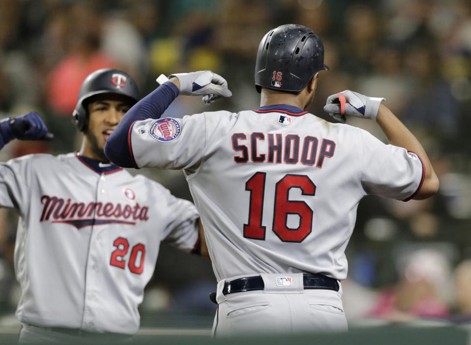 Minnesota Twins' Jonathan Schoop celebrates with Eddie Rosario (20) after hitting a two-run home run off Seattle Mariners' Ryan Garton during the sixth inning of a baseball game Saturday, May 18, 2019, in Seattle. (AP Photo/John Froschauer)