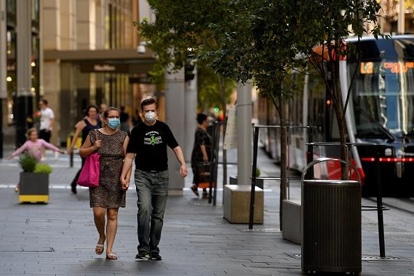 People wearing face masks walk in the empty streets of Sydney's central business district on Easter Saturday in Sydney.